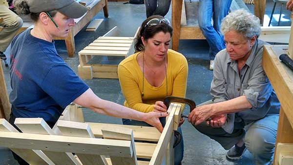Workshop Assistant Alex Cotter (center) works with a student in 2015's Really Basic Woodworking course