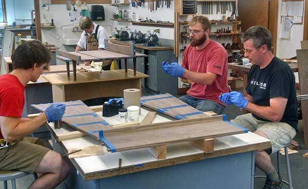 Workshop Assistant Dave Messmer (center) helps Instructor Ray Finan with a student's glue up in 2015's Cabinets and Casepeices course