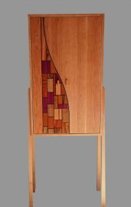 """Alan Kalker   Madison, WI. Stained Glass Wine Cabinet, 2020. Cherry, assorted exotic woods. $3,600. 60"""" x 22"""" x 15.5""""."""