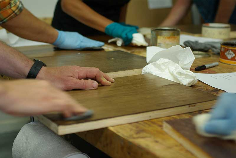Students rub out panels with wax-charged steel wool to create a desirable sheen and surface.