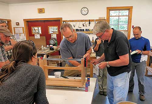 Peter Korn (center) and student gluing up a bench